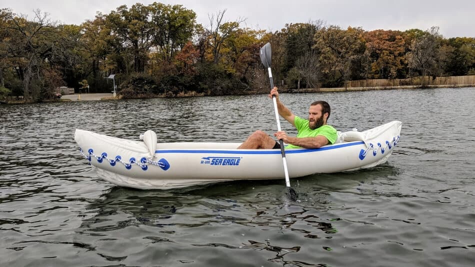 paddler in an inflatable kayak on a lake