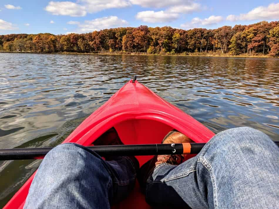 demonstrating the stability of a hardshell kayak while on a lake in the fall