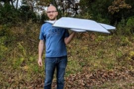 holding my inflatable boat floor made from corrugated plastic with one hand on a fall day
