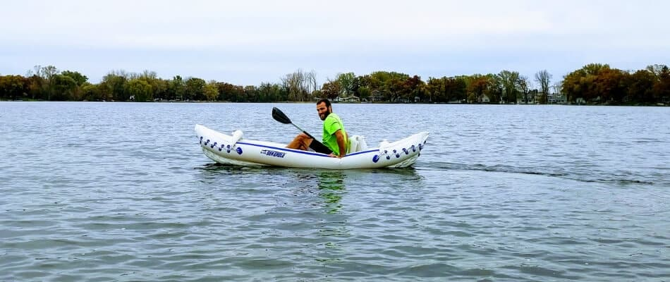paddler in an inflatable kayak on a lake taking a break to stretch out his core