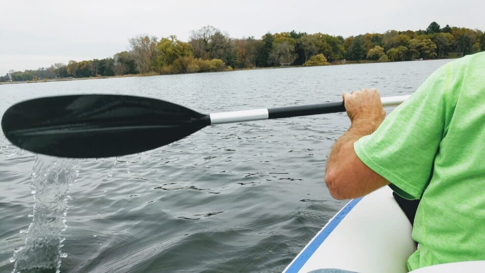 paddler in an inflatable kayak on a lake showing how far to raise the paddle out of the water on a stroke