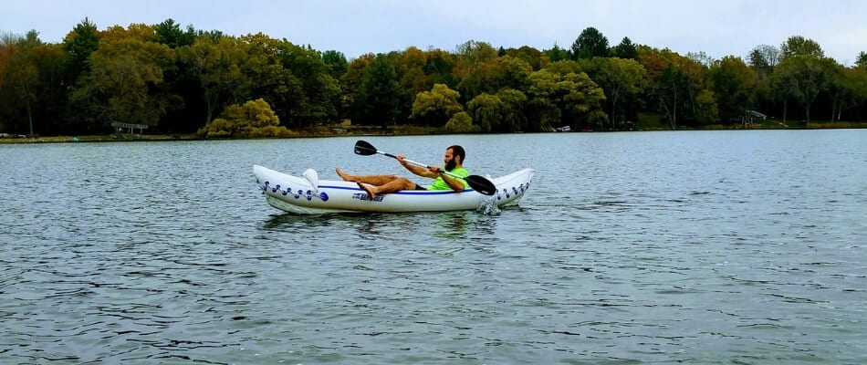 paddler in an inflatable kayak on a lake demonstrating an alternative position for legs