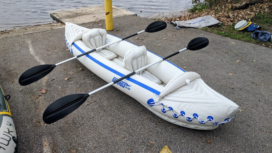 inflated Sea Eagle 330 inflatable kayak on boat landing with both oars laying across