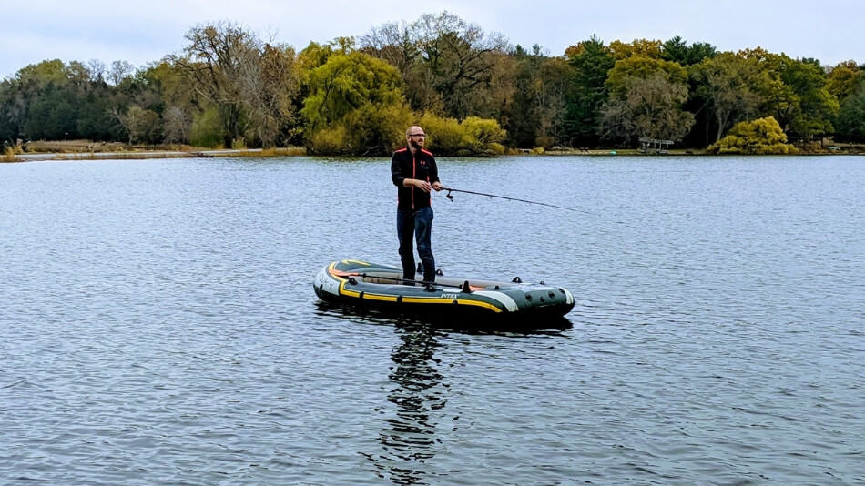 paddler demoing the stability of an inflatable boat by standing while out on a lake