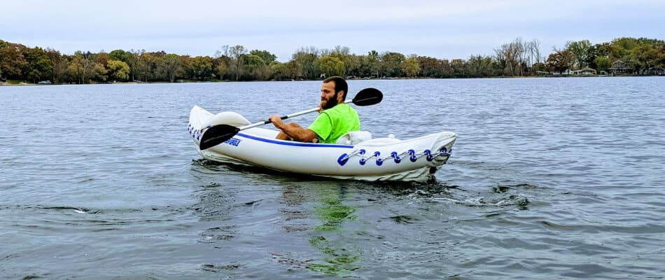 paddler in an inflatable kayak on a lake showing technique