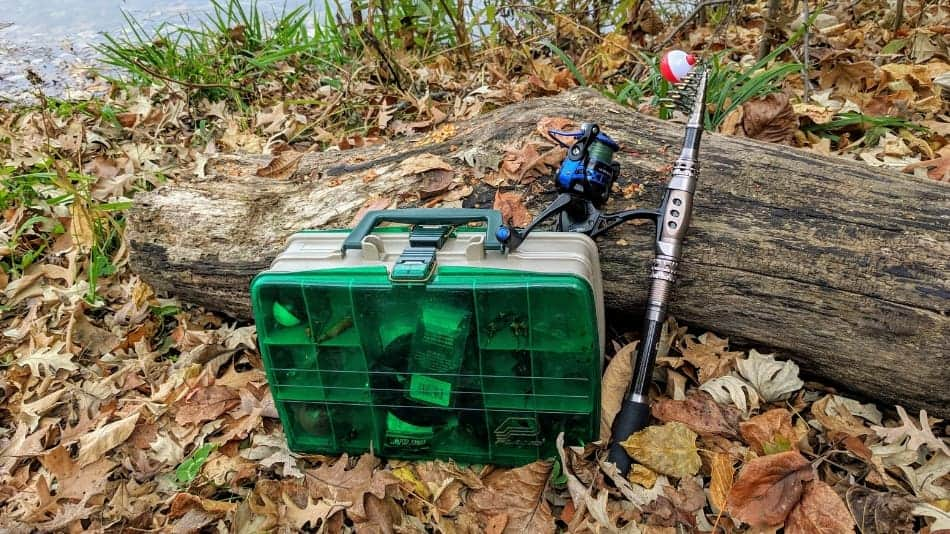collapsible fishing pole and a tackle box on the shore of a lake