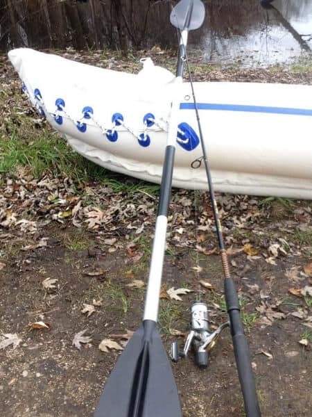 fishing pole and a kayak paddle on an inflatable kayak at a river side
