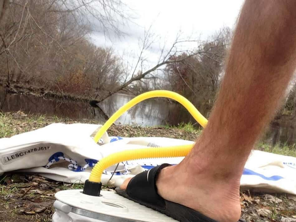 pumping up an inflatable kayak with a foot pump at the side of a river