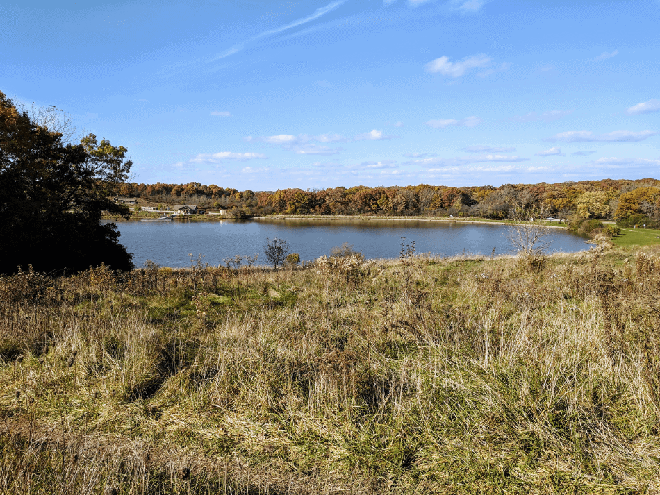 view of a small lake from a hill on a sunny day